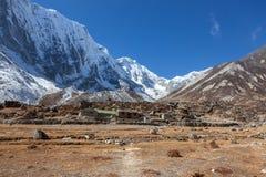 Sneeuwhimalayan-bergen en Nepali-dorp binnen Royalty-vrije Stock Afbeeldingen