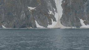 Sneeuwklip op rotsachtig eiland Weergeven van schip die voorbij sneeuwberg en klip varen stock videobeelden