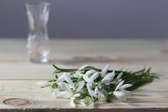 Sneeuwklokjes op de lijst De lente bloeit boeket Sneeuwklokjesachtergrond De lentebloemen op de houten lijst Vakantiebureau Vakan stock fotografie