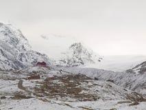 Sneeuwlandschap met grintachtige weg Nevelige scherpe pieken van hooggebergte op achtergrond Royalty-vrije Stock Afbeeldingen