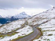 Sneeuwlandschap met grintachtige weg Nevelige scherpe pieken van hooggebergte op achtergrond Royalty-vrije Stock Foto's