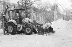Sneeuwmachine met een stad van de emmer openluchtstraat Royalty-vrije Stock Foto