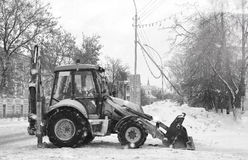 Sneeuwmachine met een stad van de emmer openluchtstraat Royalty-vrije Stock Afbeeldingen