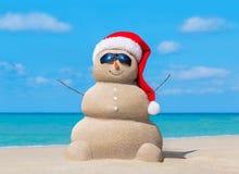 Sneeuwman in de hoed van de Kerstmiskerstman en zonnebril bij oceaanstrand Stock Foto