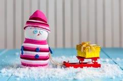 Sneeuwman die van een arrit met met de hand gemaakte gift genieten Royalty-vrije Stock Foto