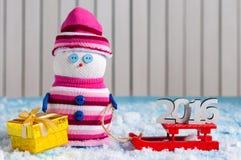 Sneeuwman die van een arrit met met de hand gemaakte gift genieten Royalty-vrije Stock Foto's