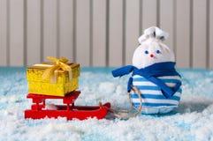 Sneeuwman die van een arrit met met de hand gemaakte gift genieten Royalty-vrije Stock Afbeeldingen