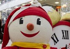 Sneeuwman in een rood GLB tegen de achtergrond van wijzerplaat dichte omhooggaand Royalty-vrije Stock Afbeeldingen