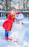 Sneeuwman en jong meisje Stock Foto