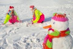 Sneeuwman en jonge vrouwen stock afbeeldingen
