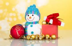 Sneeuwman en Kerstmisballen op gele achtergrond Stock Foto's