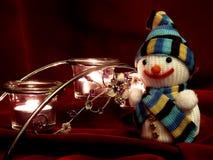 Sneeuwman en van de kaarsen donkerrode stof achtergrond Royalty-vrije Stock Afbeeldingen