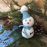 Sneeuwman met de hand gemaakt stuk speelgoed op een nette tak royalty-vrije stock fotografie