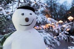 Sneeuwman met hoed voor sneeuw behandelde bomen bij nacht Stock Afbeelding
