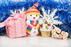 Sneeuwman met roze giftdoos en witte sneeuwvlokken Stock Foto's