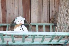 Sneeuwman op een ladder stock fotografie
