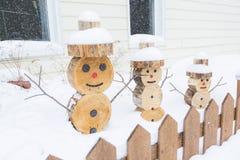 Sneeuwman in stuk van hout met omheining op de voorzijde wordt gemaakt die Stock Afbeeldingen