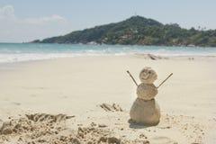Sneeuwman van zand op een achtergrond van het tropische warme overzees wordt gemaakt die Stock Afbeelding