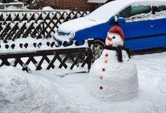 Sneeuwman voor een huis in de stad Stock Afbeeldingen