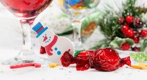 Sneeuwmandecoratie, wijn en snoepjes op een Kerstmislijst stock fotografie