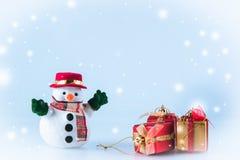 Sneeuwmantribune dichtbij giftdoos op witte achtergrond Stock Foto