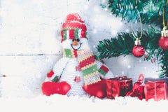 Sneeuwmanzitting op de sneeuw met Kerstmisboom Royalty-vrije Stock Afbeelding