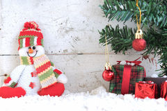 Sneeuwmanzitting op de sneeuw met Kerstmisboom in uitstekende achtergrond Royalty-vrije Stock Afbeeldingen