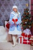 Sneeuwmeisje die (Snegurochka) een Nieuwjaargift houden Royalty-vrije Stock Fotografie