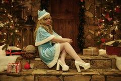 Sneeuwmeisje op drempel van huis in Kerstmisstijl die wordt verfraaid Stock Afbeeldingen