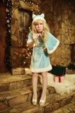Sneeuwmeisje op drempel van huis in Kerstmisstijl die wordt verfraaid Stock Fotografie