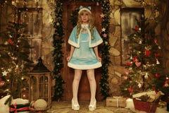 Sneeuwmeisje op drempel van huis in Kerstmisstijl die wordt verfraaid Stock Afbeelding
