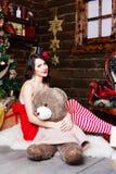 Sneeuwmeisje in rode kleding met een beer die op Kerstboomachtergrond glimlachen Royalty-vrije Stock Fotografie