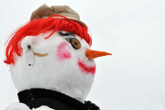 Sneeuwmens met rode pruik, zwarte sjaal en bonnet stock foto
