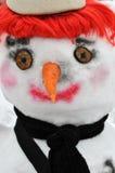 Sneeuwmens met rode pruik, zwarte sjaal en bonnet stock afbeeldingen