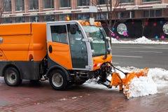 Sneeuwploeg schoonmakende bestratingen en straten die in sneeuw en modder tijdens zware sneeuwval behandeld zijn Royalty-vrije Stock Afbeelding
