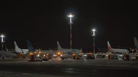 Sneeuwploegvrachtwagens die tarmac in Vnukovo-Luchthaven bij nacht, Moskou schoonmaken stock videobeelden