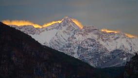 Sneeuwpoeder in de hemel door sterke die wind wordt opgeheven en door het oranje licht dat van de kleurenzonsondergang wordt aang Stock Afbeeldingen