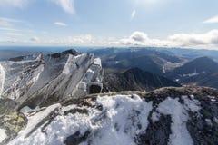 Sneeuwrotsen in de voorgrond en de reusachtige berg op de achtergrond in de bergen van het Subpolaire Oeralgebergte Stock Fotografie