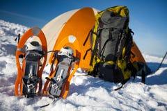 Sneeuwschoenen verlaten voor oranje tent Royalty-vrije Stock Foto