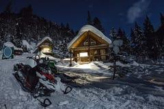 Sneeuwscooter van huischalets in de winterbos met sneeuw in ligh stock afbeeldingen