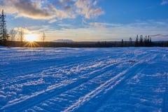 Sneeuwscootersporen in zonsondergang Royalty-vrije Stock Afbeeldingen
