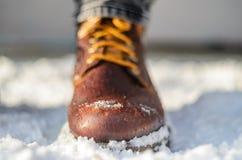 Sneeuwsmeltingen op bruine de winterlaarzen Bruine leerschoenen in de sneeuw stock afbeelding