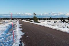 Sneeuwstaak door een landwegkant in een duidelijk landschap Stock Afbeelding