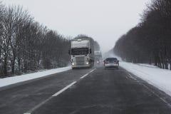 Sneeuwstorm op spoor met auto's het berijden Stock Foto's