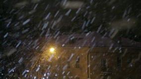 Sneeuwval in de stad bij nacht door het licht van een straatlantaarn stock videobeelden