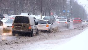 Sneeuwval in de stad, de stroom van auto's het drijven op de weg door een vulklei stock footage