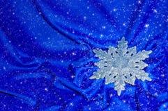 Sneeuwvlok op een blauwe zijde met fonkelingen Stock Afbeeldingen