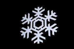 Sneeuwvlok op zwarte achtergrond wordt geïsoleerd die: macrofoto van echt die sneeuwkristal, op glas met LEIDEN achterlicht wordt stock fotografie