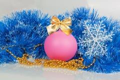 Sneeuwvlokken en roze Kerstmisbal met blauwe slinger en gouden Stock Foto's