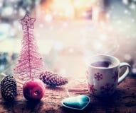Sneeuwvlokkenmok met hete drank en Kerstmisdecoratie op venstervensterbank met sneeuw royalty-vrije stock fotografie